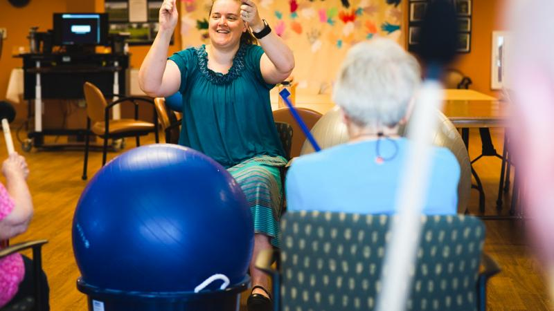 Melissa Cole, center, music therapist at Oakwood Village in Madison, Wisconsin, sings with residents.